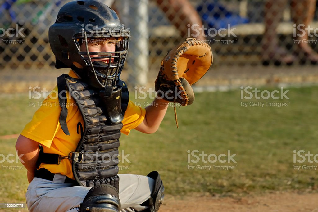 Young boy playing catcher in Little League baseball game stock photo