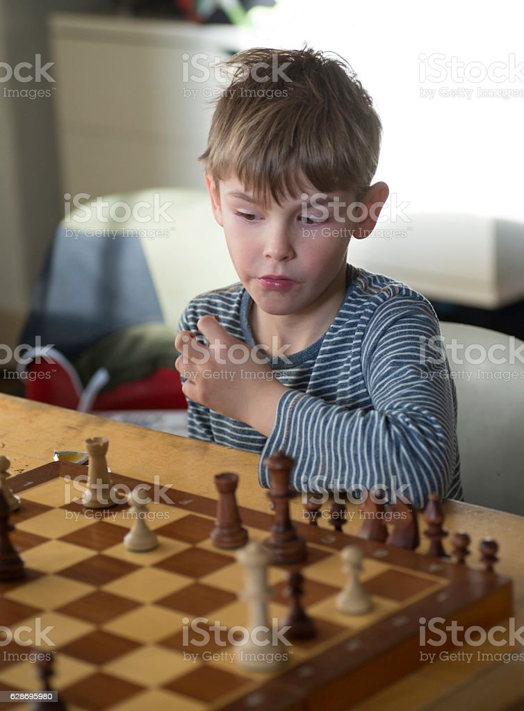 Young boy playing chess 2 stock photo