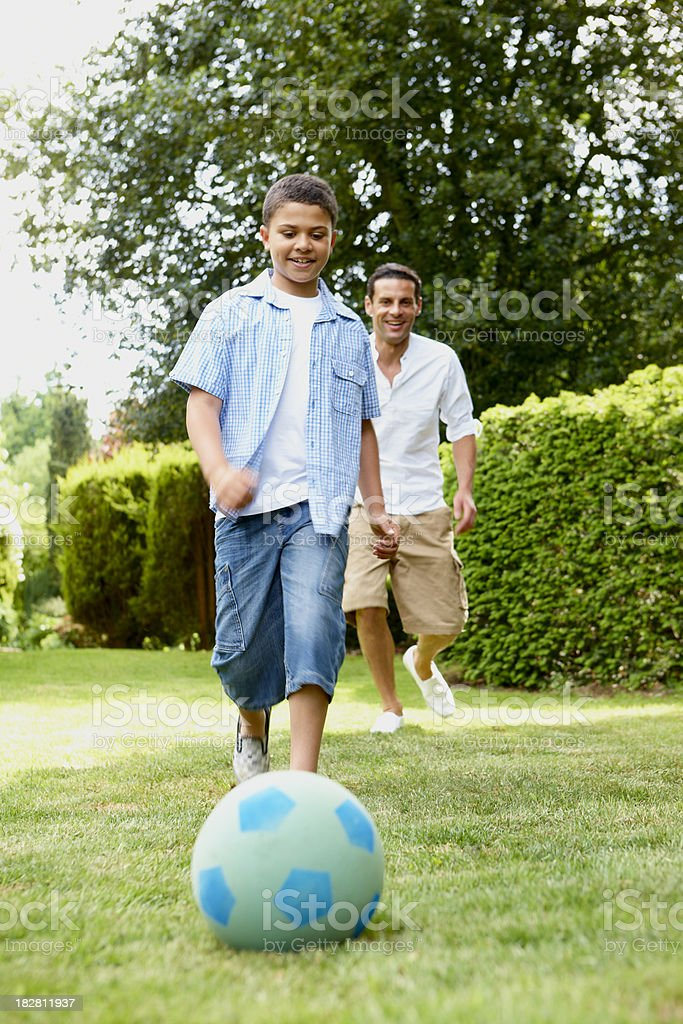 young boy playing football in garden with his father royalty-free stock photo