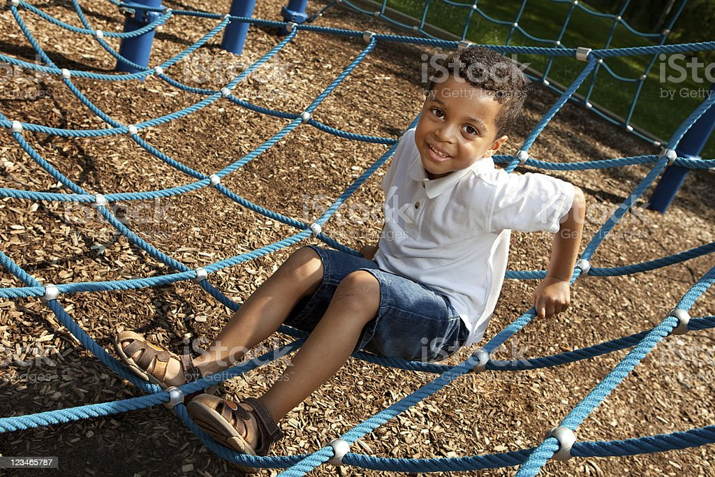 Young boy playing in a rope structure stock photo