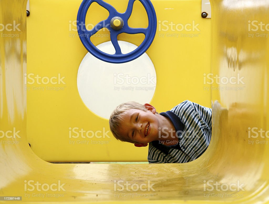 Young Boy Playing In A Yellow Tube At Playground royalty-free stock photo