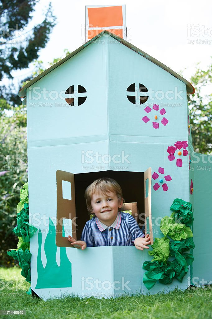 Young Boy Playing In Home Made Cardboard House stock photo