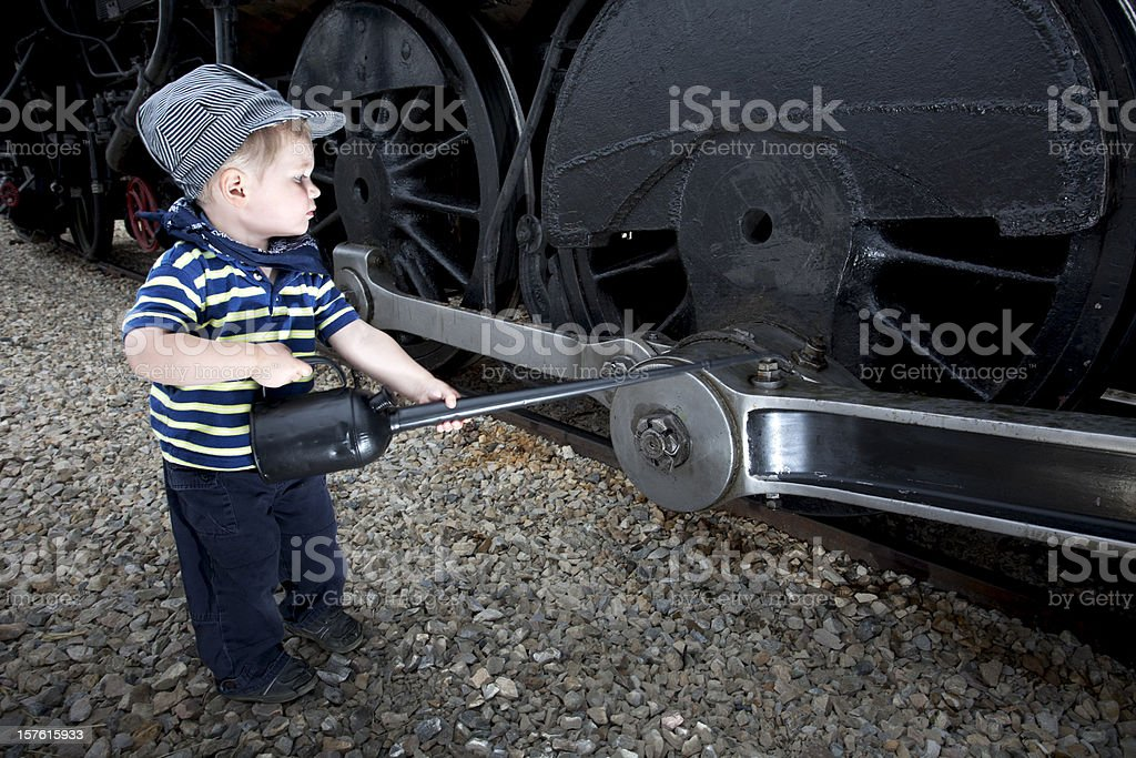 Young Boy Playing Mechanic on a Old Steam Train. stock photo
