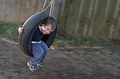 Young Boy Playing Outside in a Tire Swing
