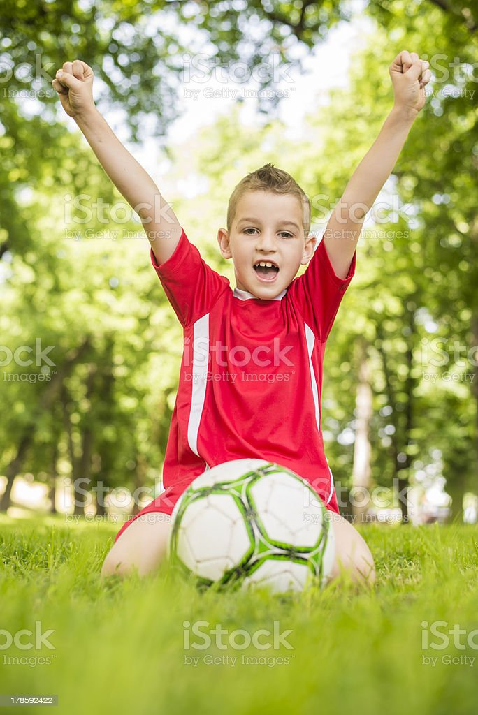 A young boy playing soccer with his arms raised stock photo
