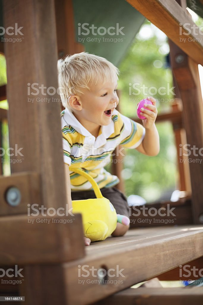 A young boy playing with a toy in a wooden playhouse stock photo