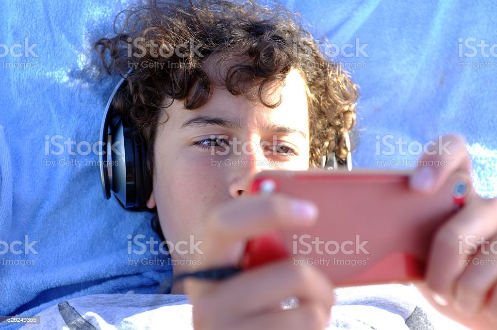 Young boy playing with his gadget stock photo