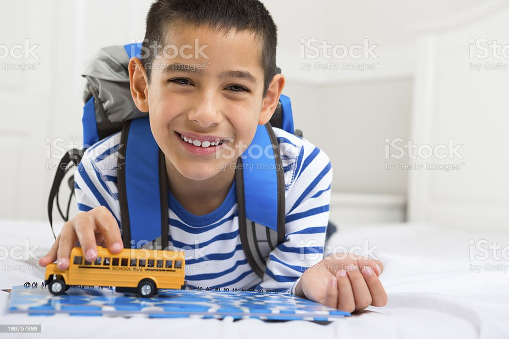 Young boy playing with his miniature toy bus royalty-free stock photo