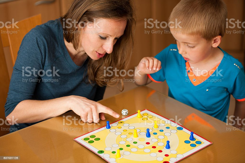 young boy plays ludo game with mother in livingroom stock photo