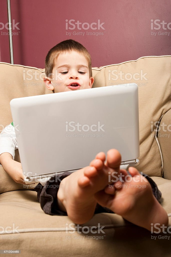 Young boy plays on a small white netbook computer stock photo