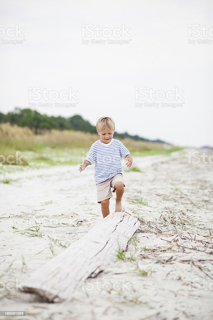 Young boy plays on log at the beach royalty-free stock photo
