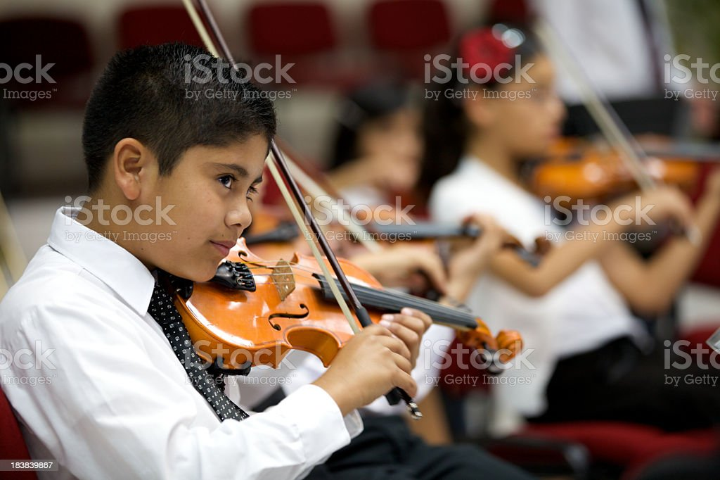 A young boy plays violin and stares outward stock photo