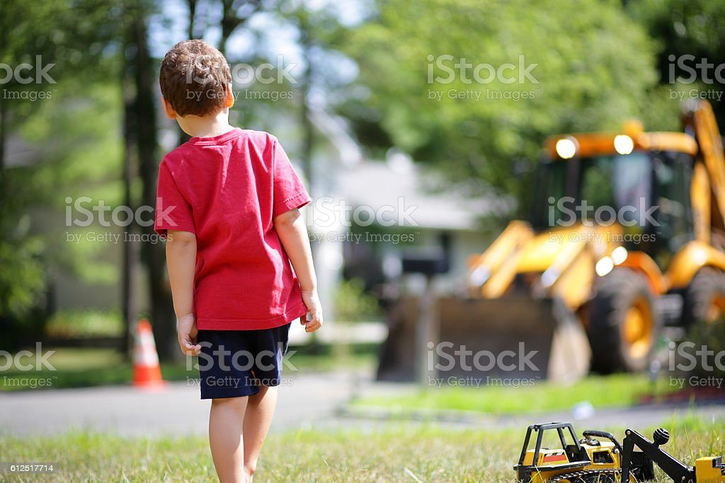 Young boy plays with his toy dump truck stock photo
