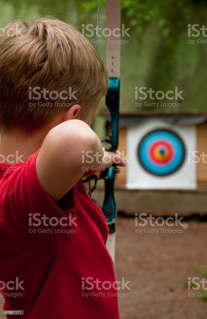 Young boy practicing archery with a bow and arrow stock photo