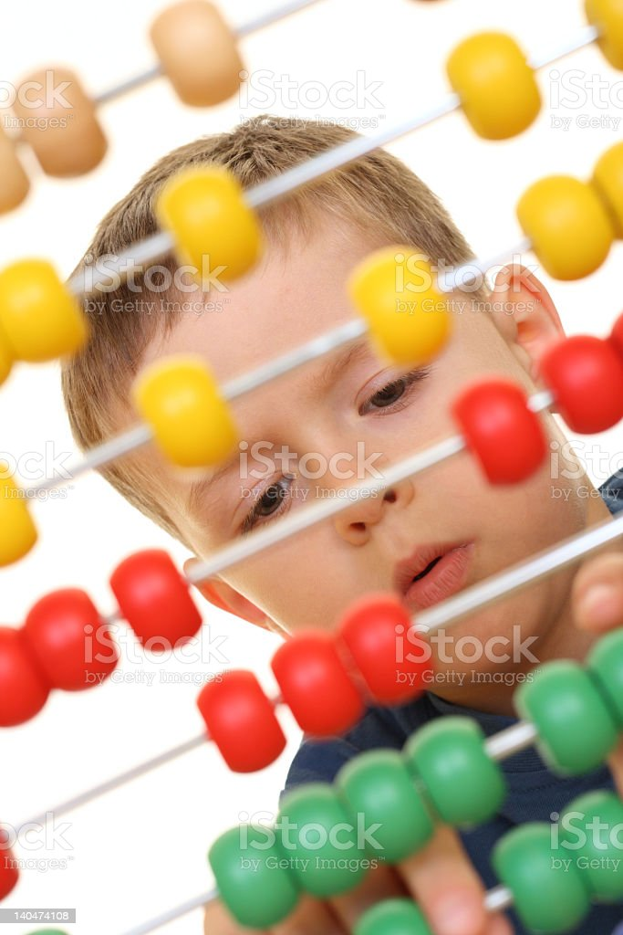 Young boy practicing math skills on homemade abacus royalty-free stock photo