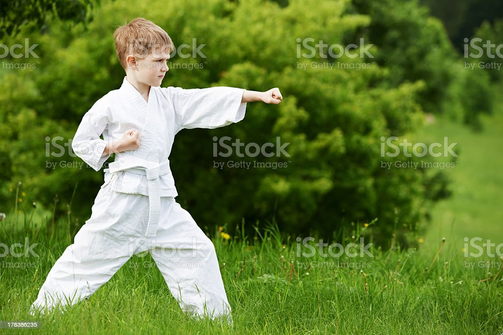 One little boy in white kimono during training karate kata exercises...