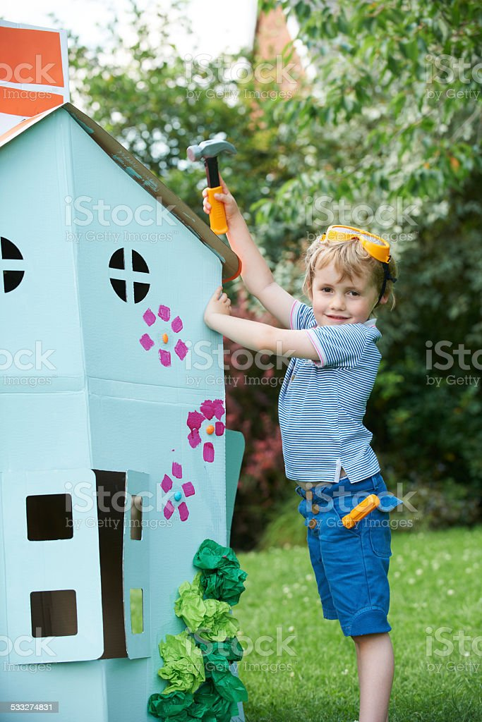 Young Boy Pretending To Fix Cardboard Playhouse stock photo