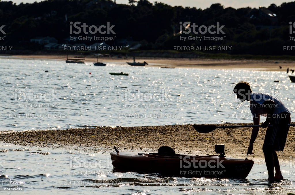 Young boy pulling kayak boat from sea in Cape Cod stock photo