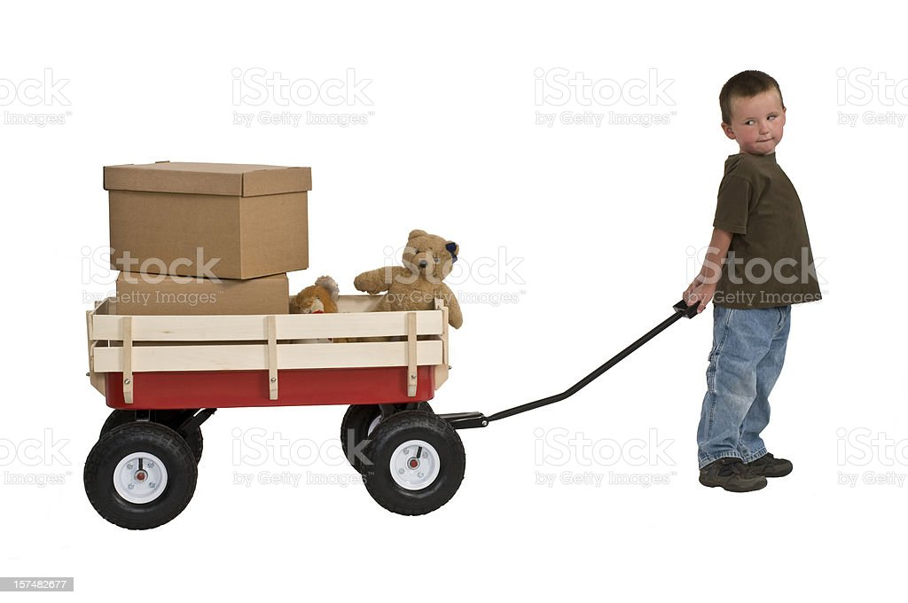 Boy Pulling Wagon : Young boy pulling wagon with boxes and teddy bears stock