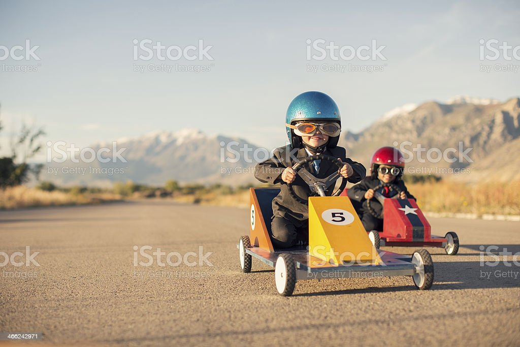 Young Boy Races Toy Car Wearing Business Suit stock photo