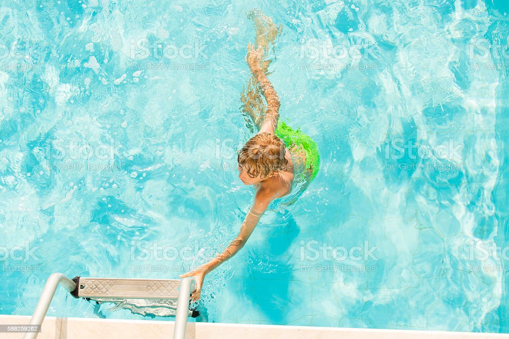 Young boy reaching for pool ladder stock photo