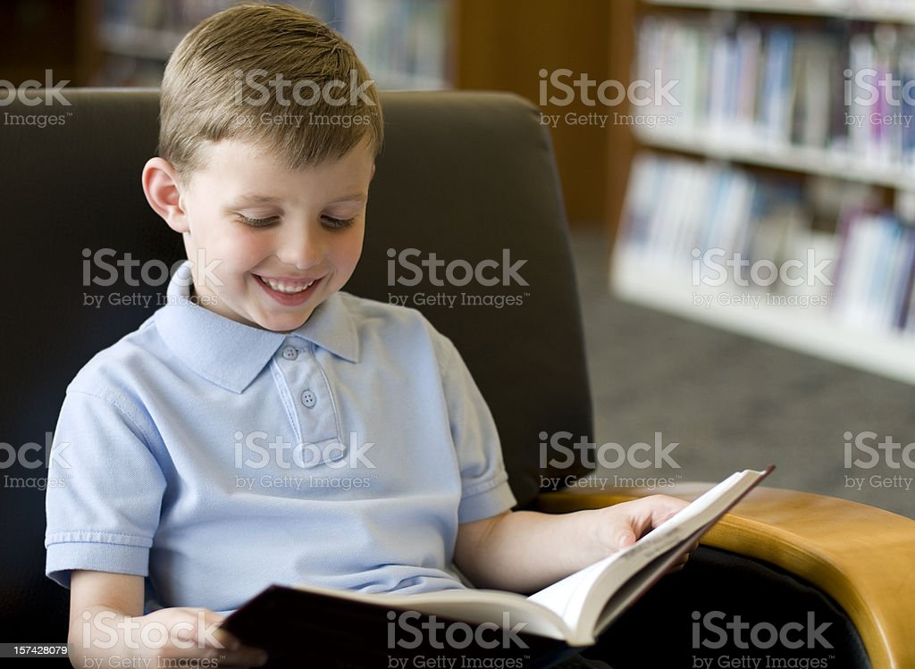 Young boy reading a book at the library royalty-free stock photo