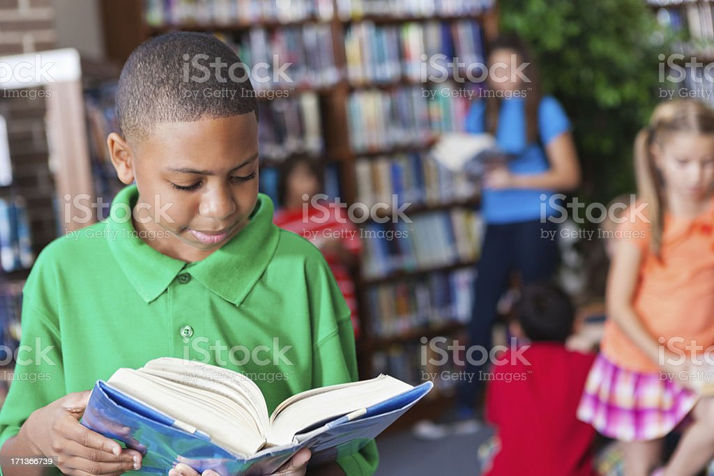 Young boy reading a book in the school library stock photo