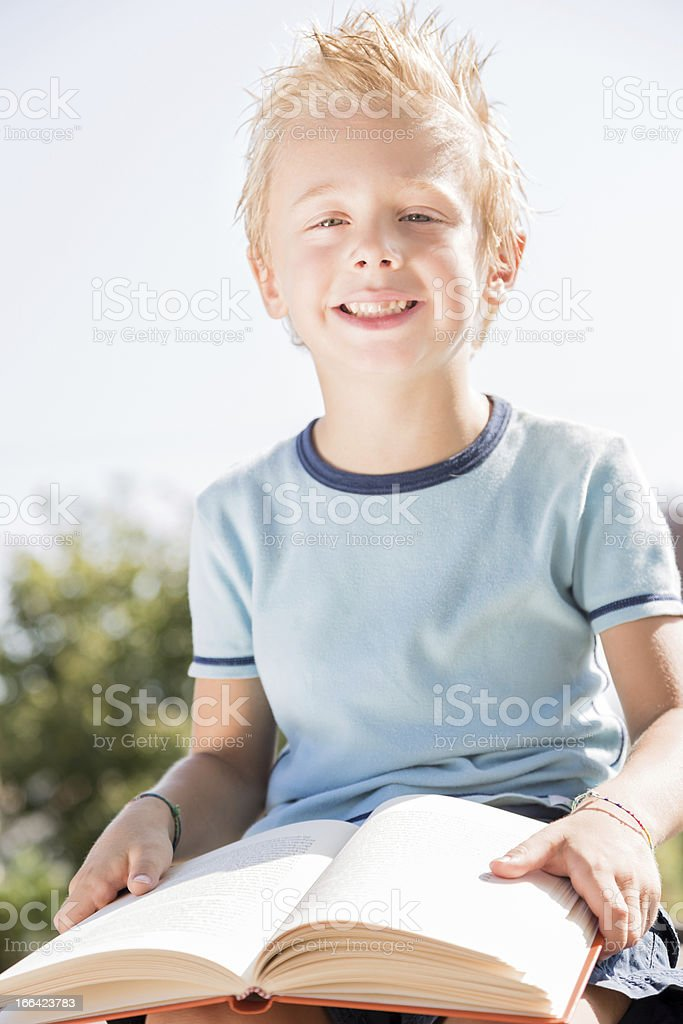 Young boy reading a book outdoor royalty-free stock photo