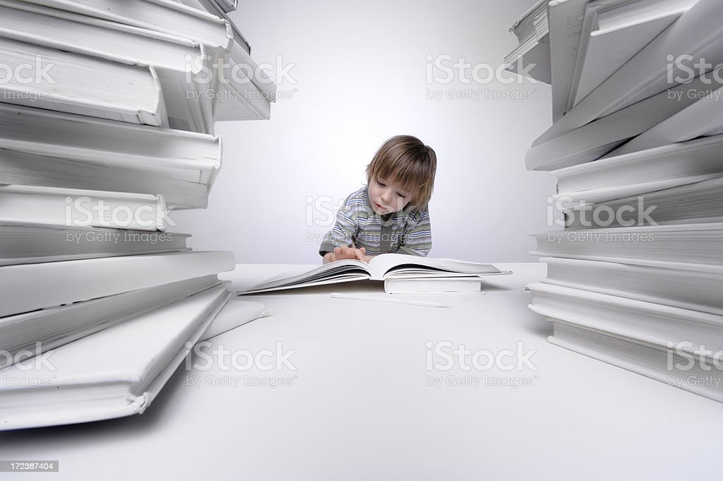 Young boy reading and doing his homework royalty-free stock photo