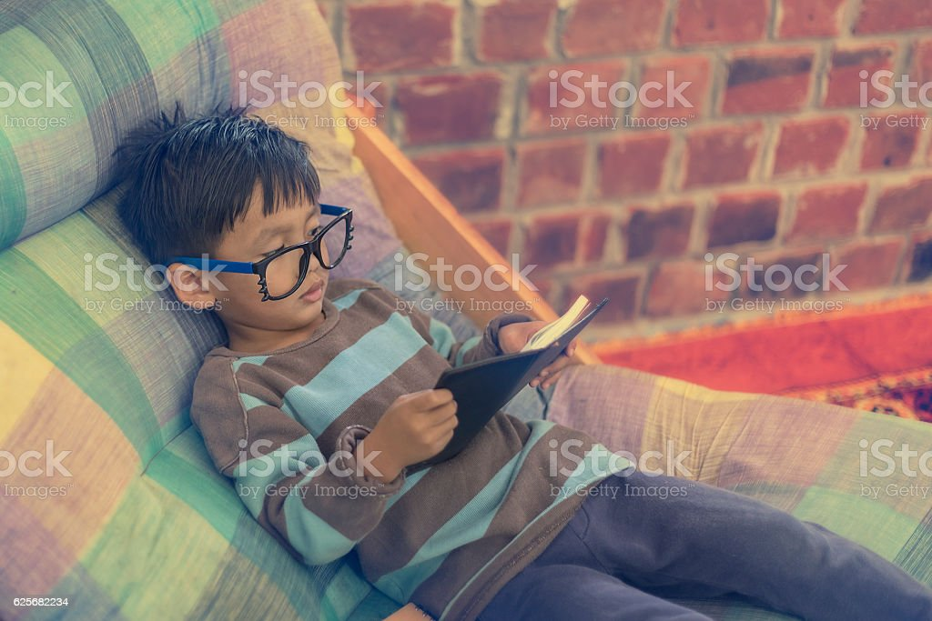 Young boy reading book on chair at home. During leisure stock photo