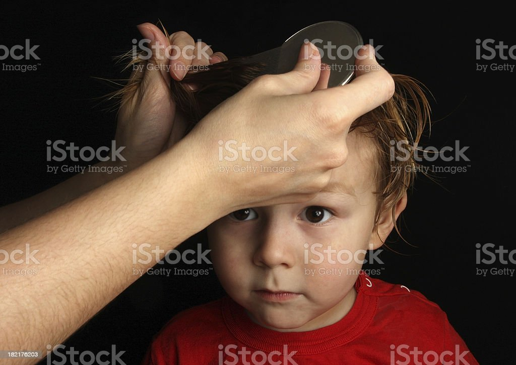 Young boy receiving a head louse treatment stock photo