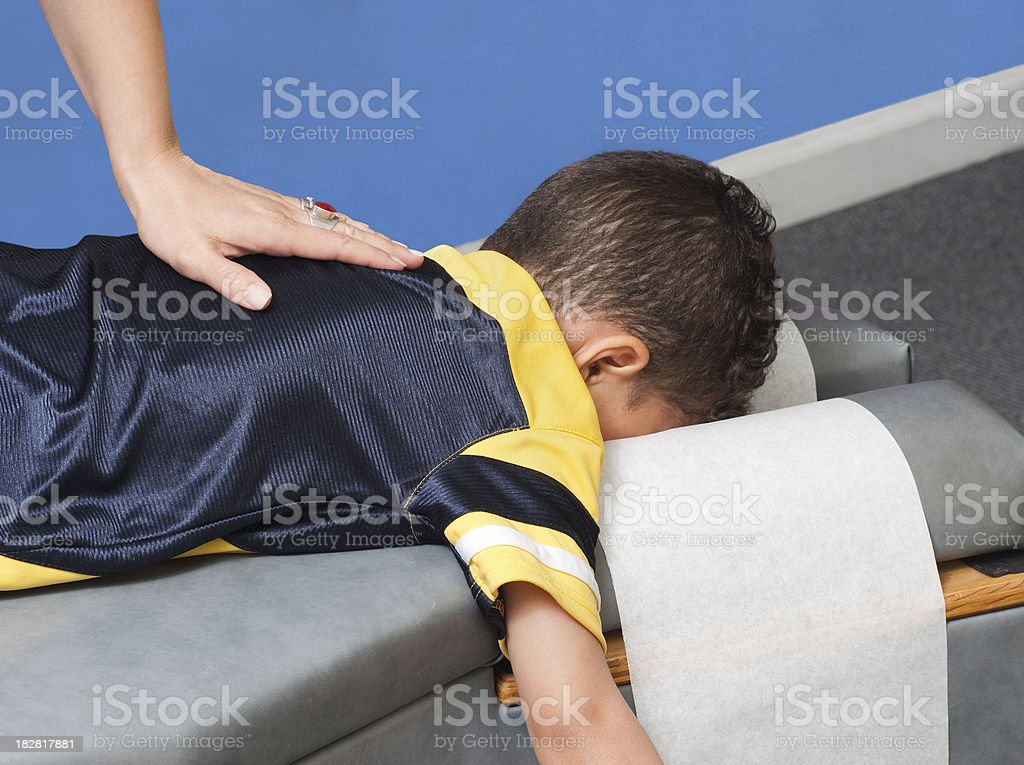 young boy receiving chiropractic care stock photo