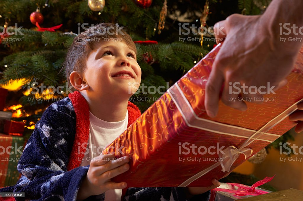 Young Boy Receiving Christmas Present In Front Of Tree stock photo