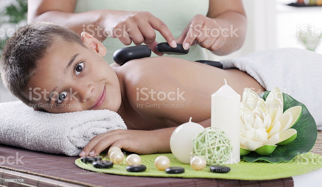 young boy  relaxing in spa. stone massage. stock photo