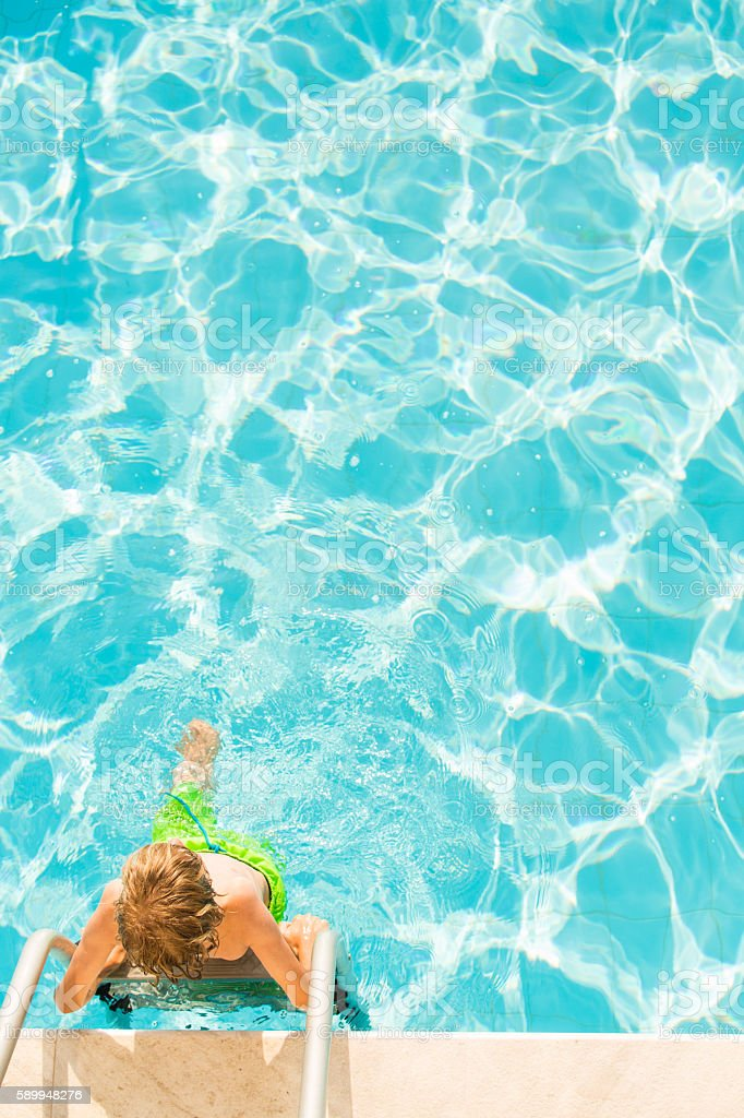 Young boy relaxing in the pool stock photo