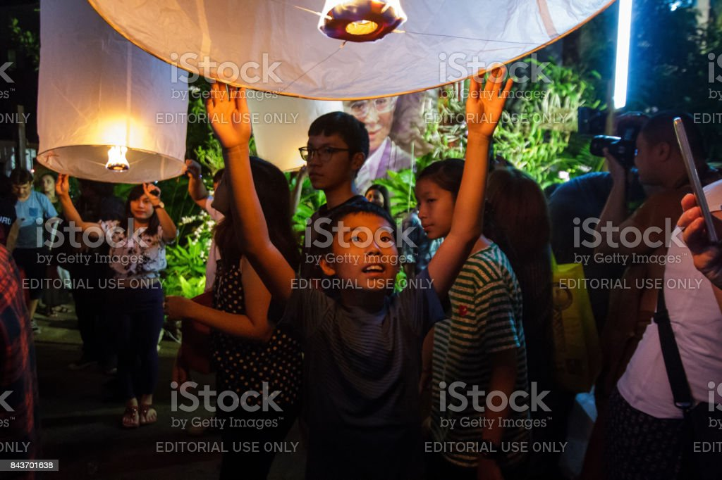 A young boy releases a floating lantern in Chiang Mai, Thailand stock photo