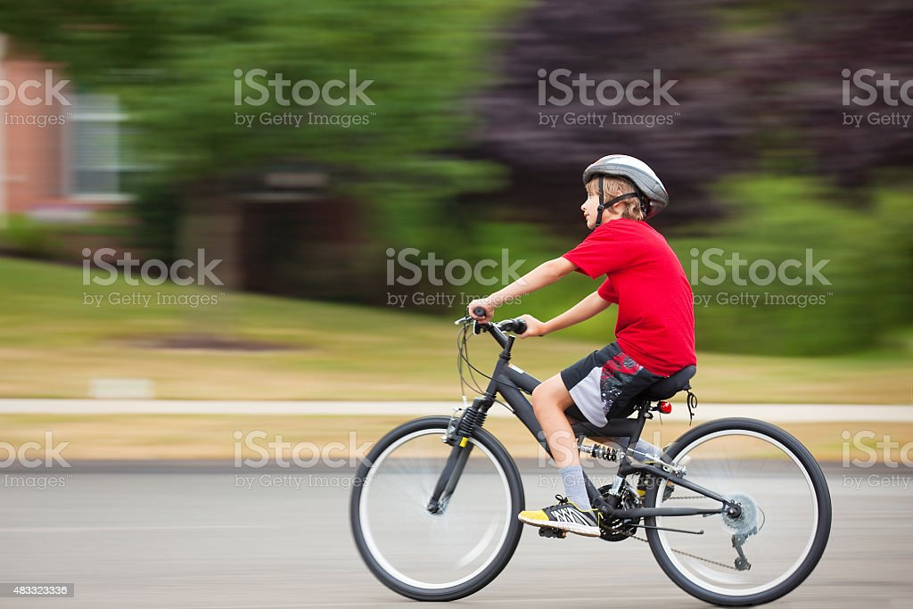 Young Boy Riding Bicycle On Residential Street stock photo