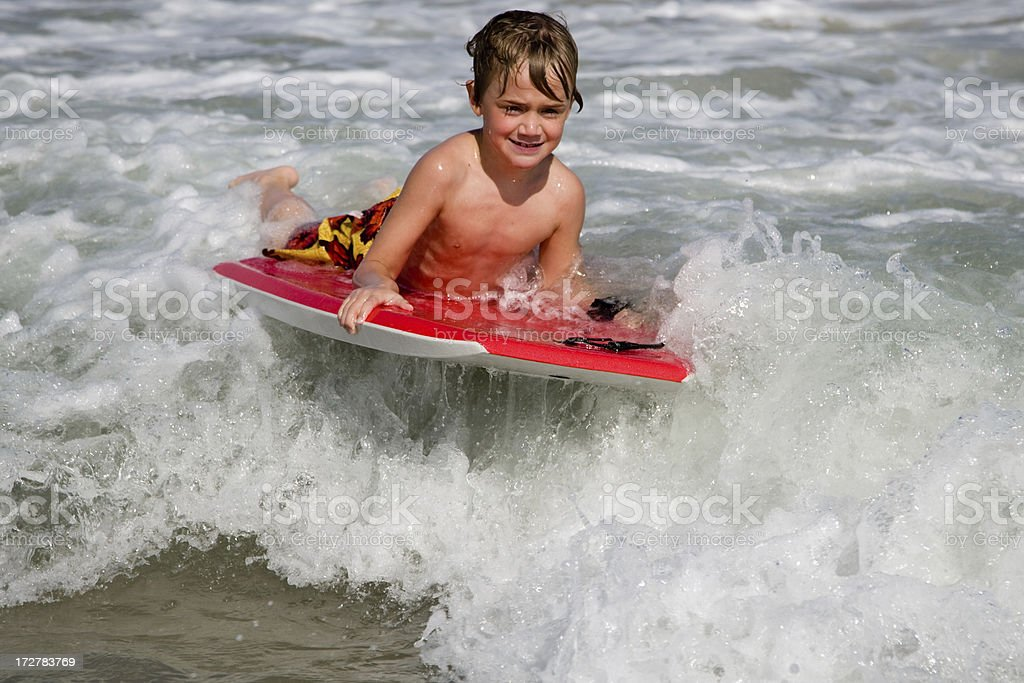 Young Boy Riding Boogie Board stock photo