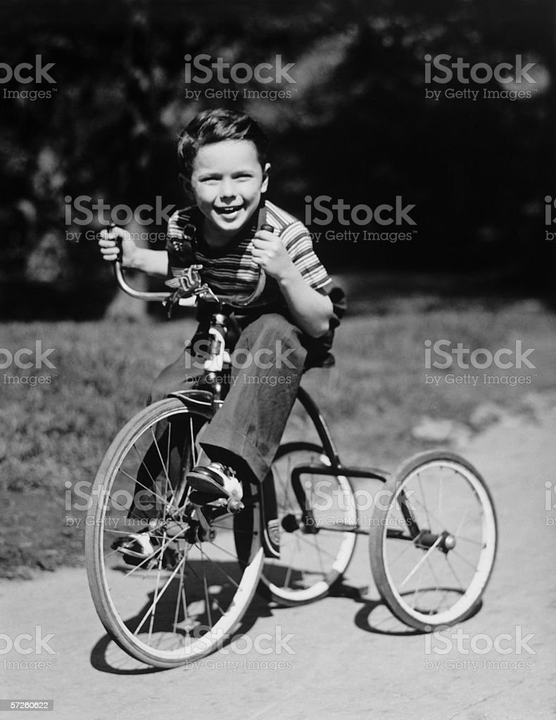 Young boy (6-7) riding tricycle in park, (B&W), portrait royalty-free stock photo