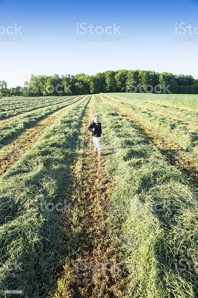 Young boy running in a farm field stock photo