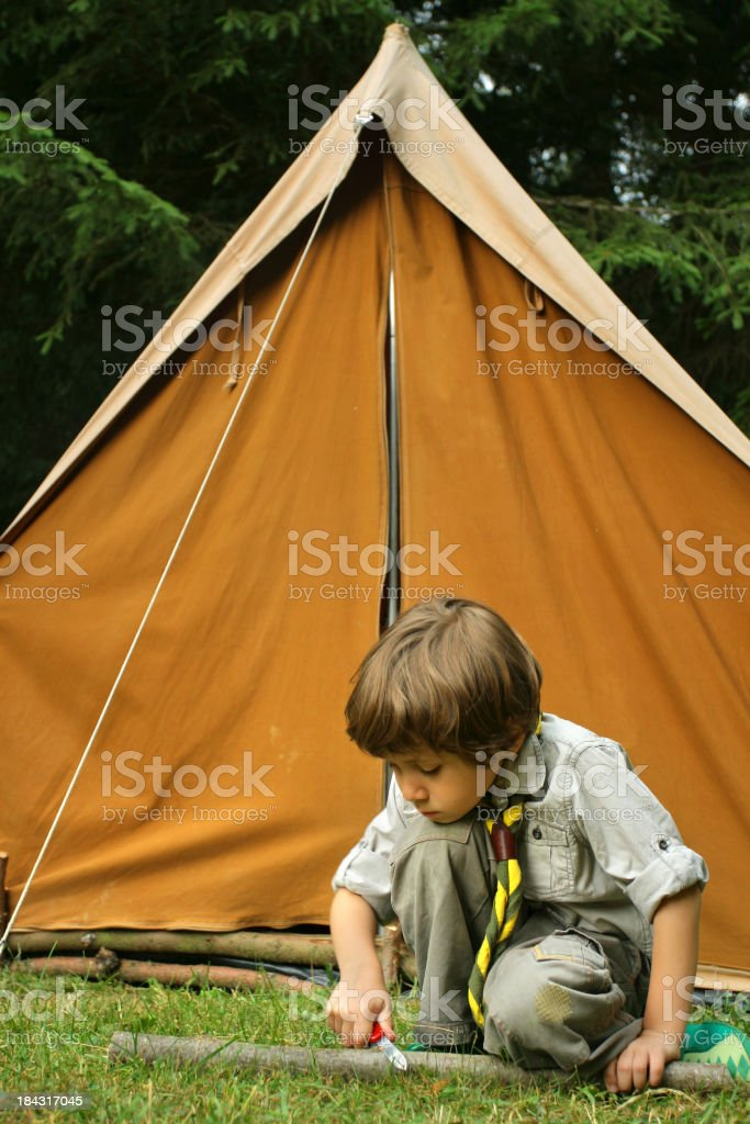Young Boy Scout carving wood in front of a tent stock photo