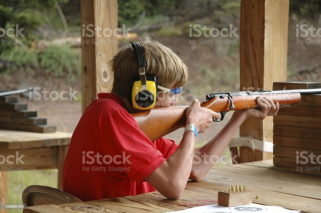 Young Boy Scout Shooting a Rifle at the Rifle Range stock photo