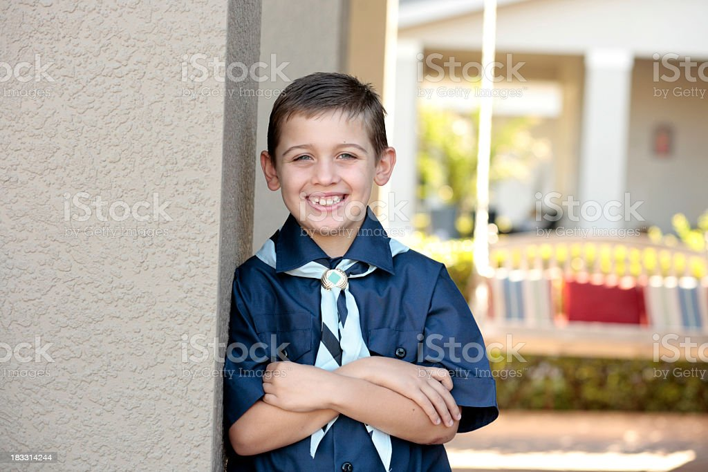 Young boy scout smiling and leaning against wall stock photo