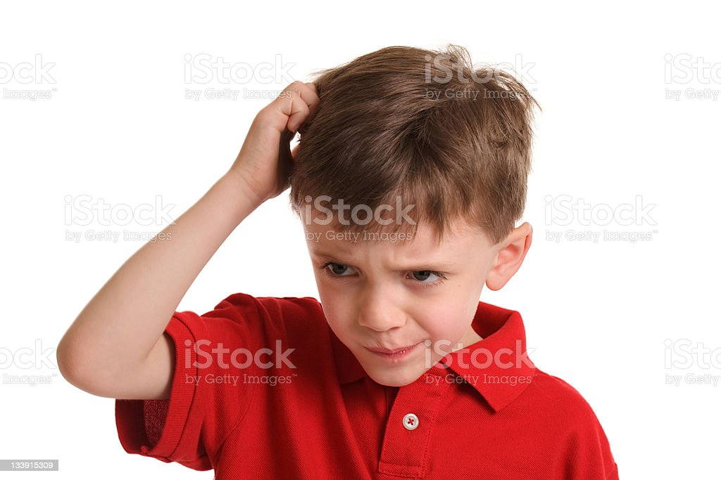 Young boy scratching his head after haircut stock photo