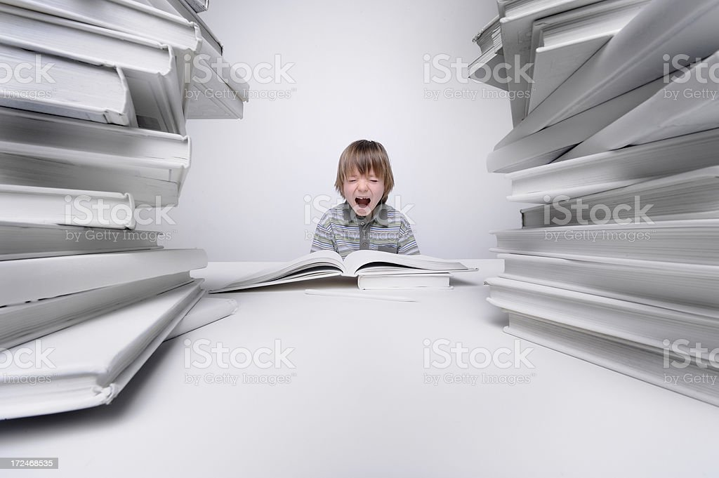 Young boy screaming with frustration over his homework royalty-free stock photo