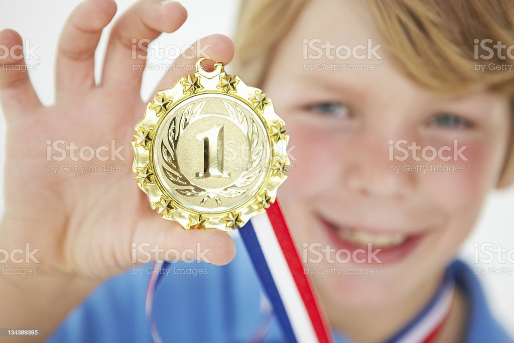 Young boy showing off medal royalty-free stock photo