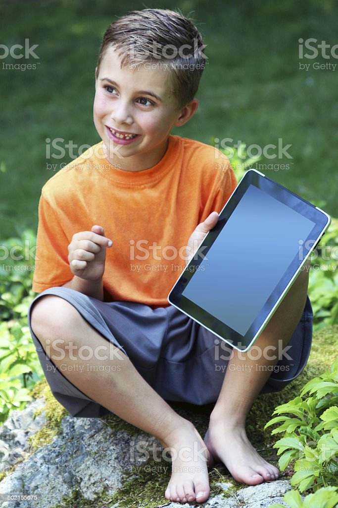 Young boy shows his touch pad with pride outdoors royalty-free stock photo