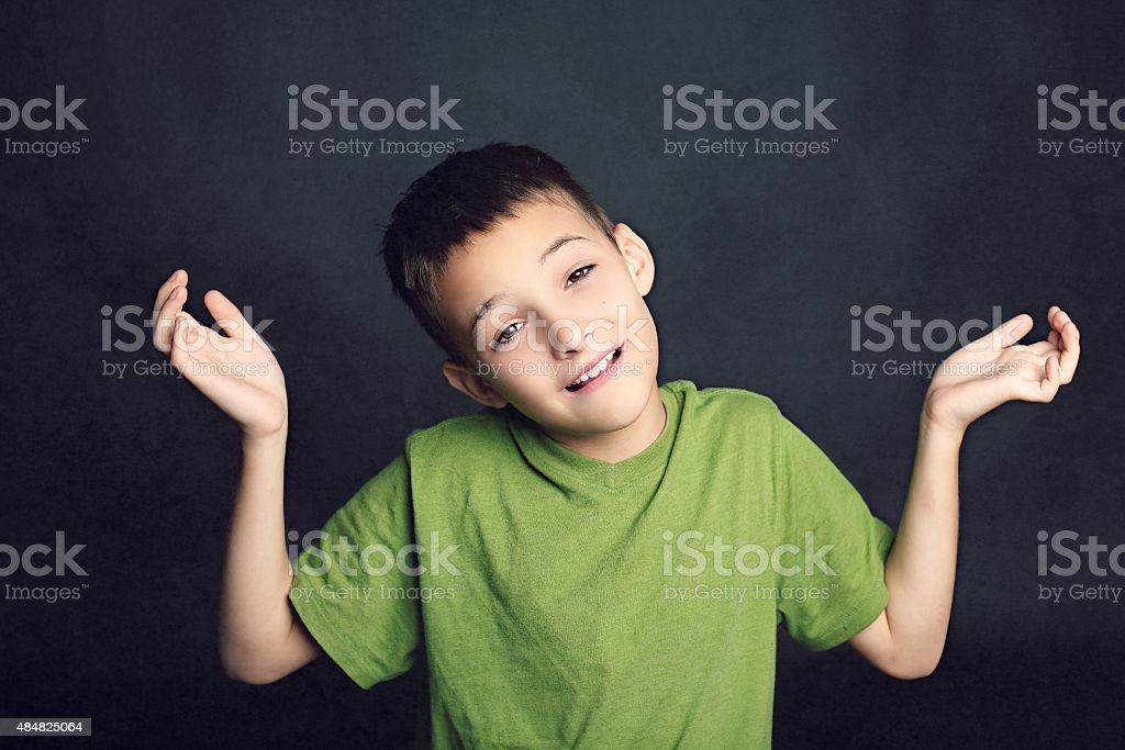 Young boy shrugging shoulders stock photo