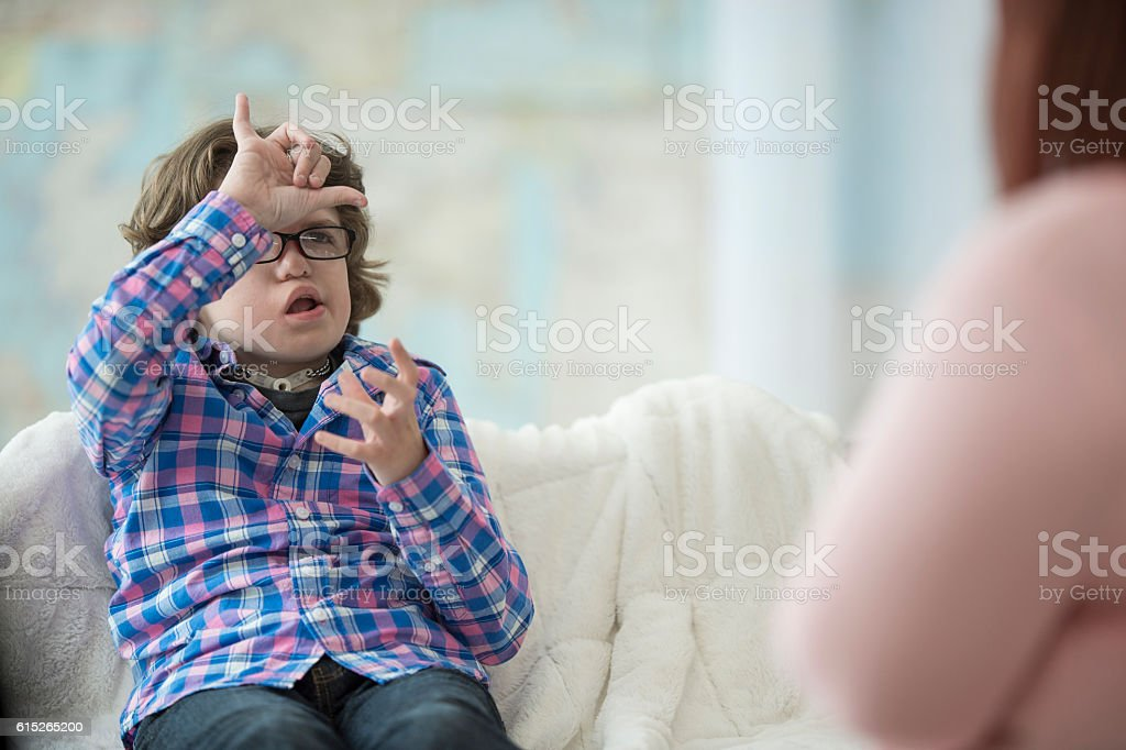 Young Boy Signing to His Tutor stock photo