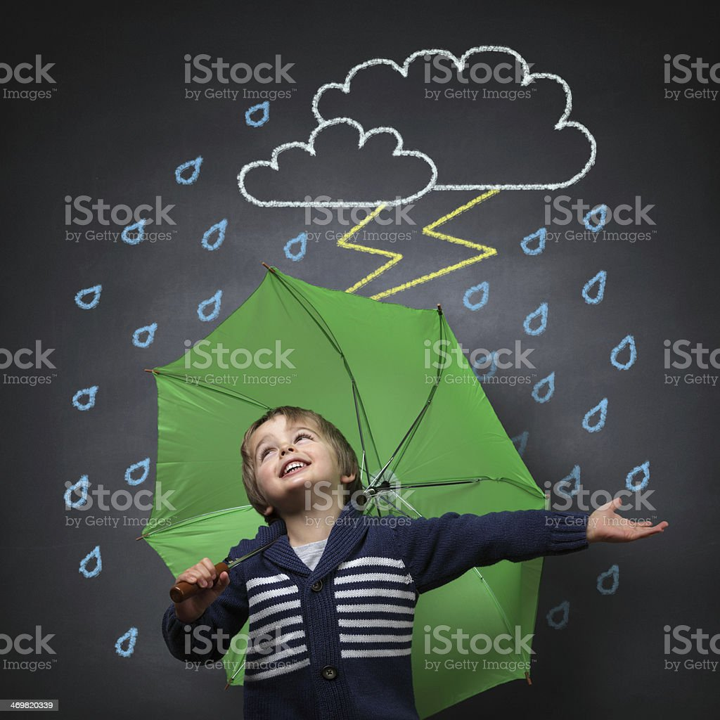 Young boy singing in the rain under a green umbrella stock photo